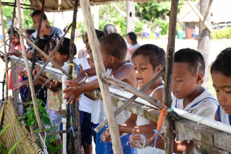 children wash their hands in school in the pacific