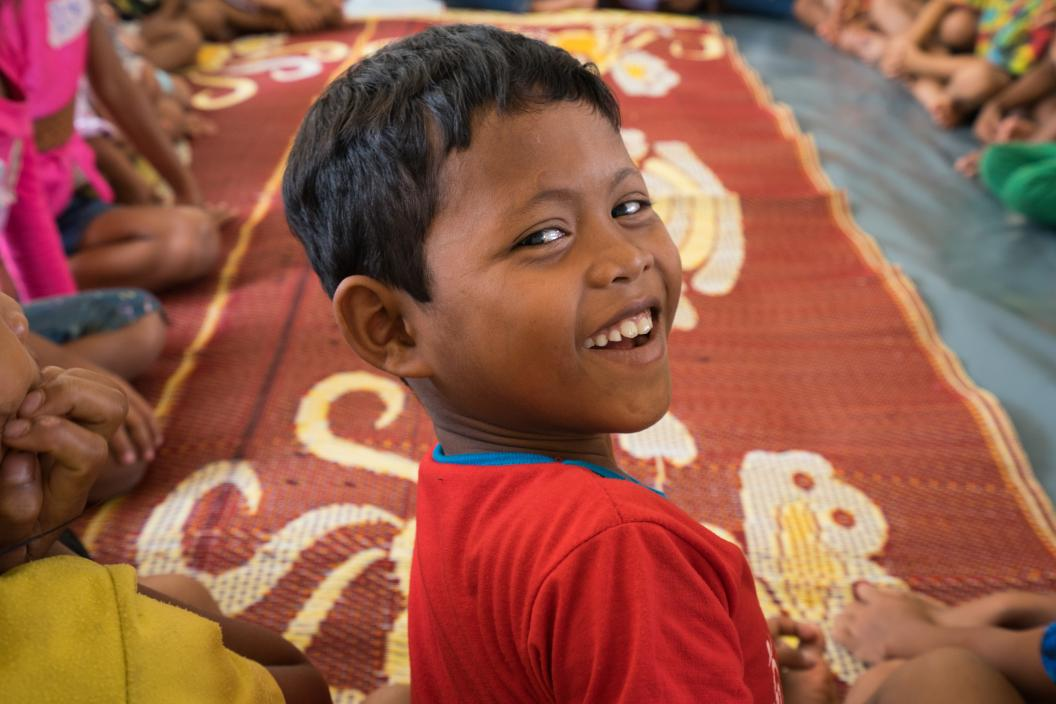 A boy smiles in a unicef supported child friendly space in southern laos