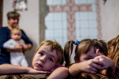 Ina Morhun, 5, and her sister Lyuda, 3, sit on a sofa at their home as their mother Iryna holds baby Vika, 1.5, in the city of Toretsk, Donetsk Oblast, Ukraine