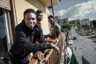 Omar (17), front, with his fellow housemates on the balcony at the reception centre where they stay in the small village of Naro, in Sicily, Italy