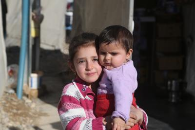 A young girl carries her baby sister in Nizip 1 refugee camp, Gaziantep, Turkey