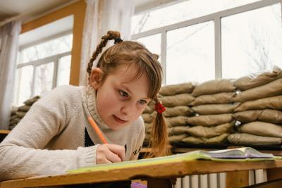 A young girl in a classroom in eastern Ukraine with windows blocked up with sandbags because of the frequent shelling.