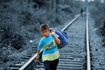 A boy carrying his belongings in a large cloth bag over his shoulder is among people walking on railway tracks to cross from the former Yugoslav Republic of Macedonia into Serbia.
