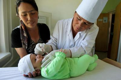 A young child receives polio vaccine at the Kizil Oy Village Primary Health Clinic in Zomin district in Jizzakh region.