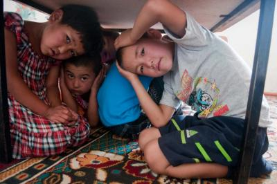 Several young children huddle under a desk looking toward the camera as part of a disaster risk reduction drill.