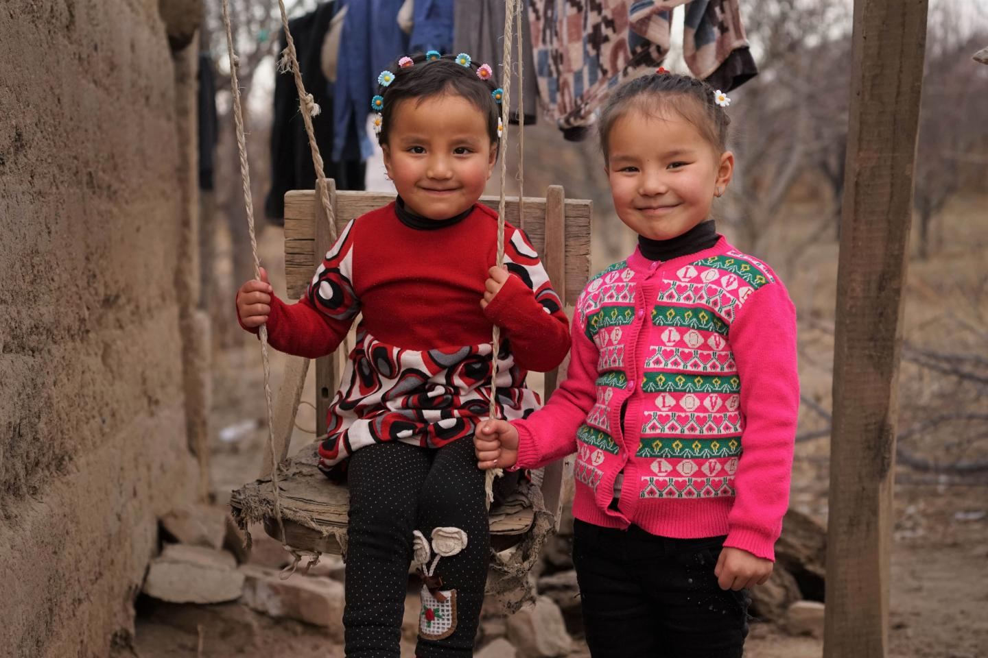 Latifa (4) (left) and her big sister Fatima (6) together in their home yard.