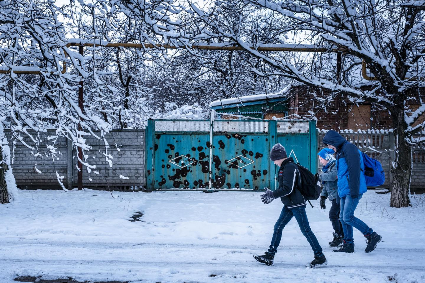 Sasha and friends walk to the bus stop past a gate damaged by shelling.