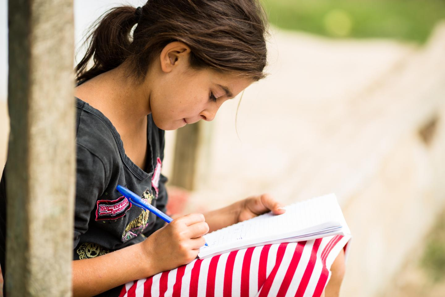 Loredana, 11 years old, sits doing her homework on the porch at her home in Romania.