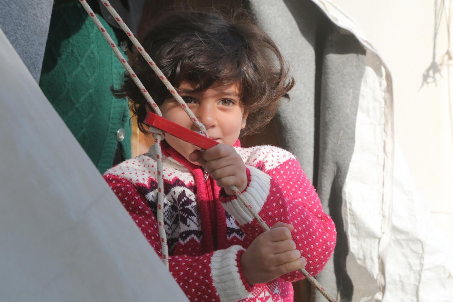 A young girl stands outside her family tent in Nizip 1 refugee camp, Gaziantep, southern Turkey.