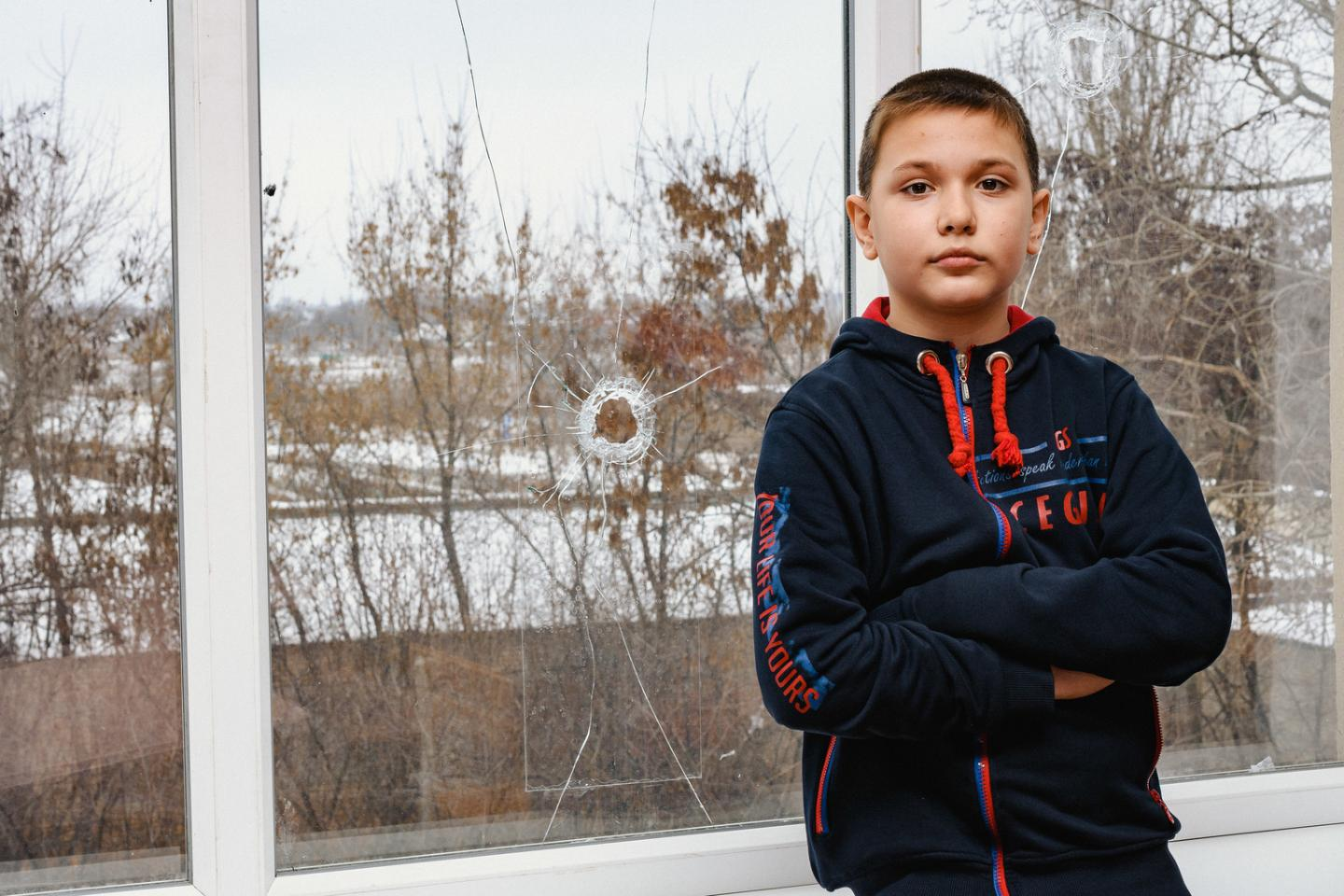Fifth grade student Rodion, 11, stands by a window damaged by a stray bullet in a classroom at school No. 2, Marinka, Donetsk region, Ukraine