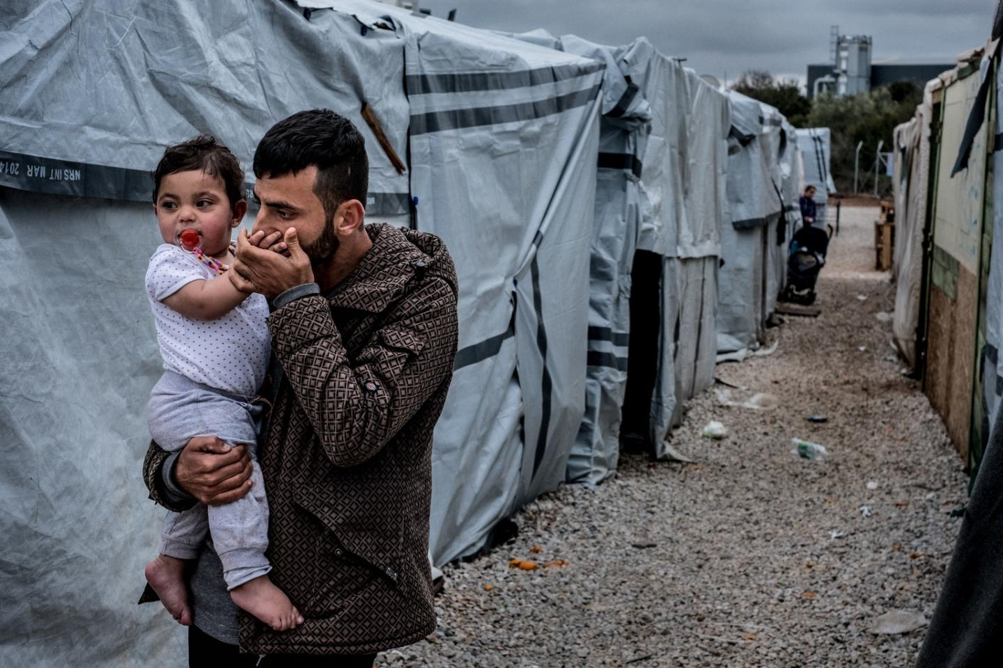 Father Barzan Hassan, from Iraq, holds one-year old Yamar, outside their shelter in Ritsona refugee camp near Chalcis, Greece.