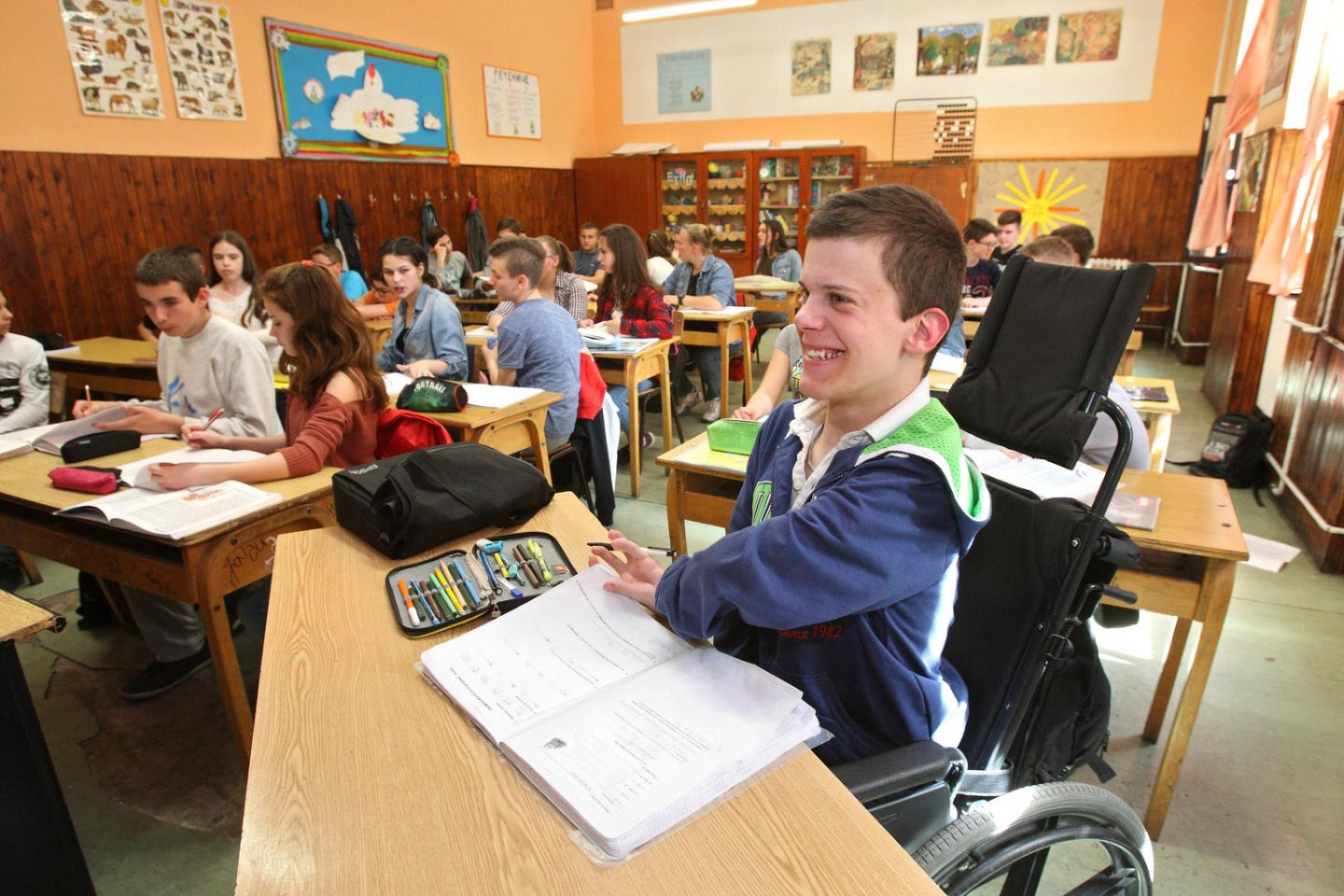 18-year-old Atlia, who was born with severely damaged limbs, smiling in class at an inclusive school in his home town of Becej in Serbia.