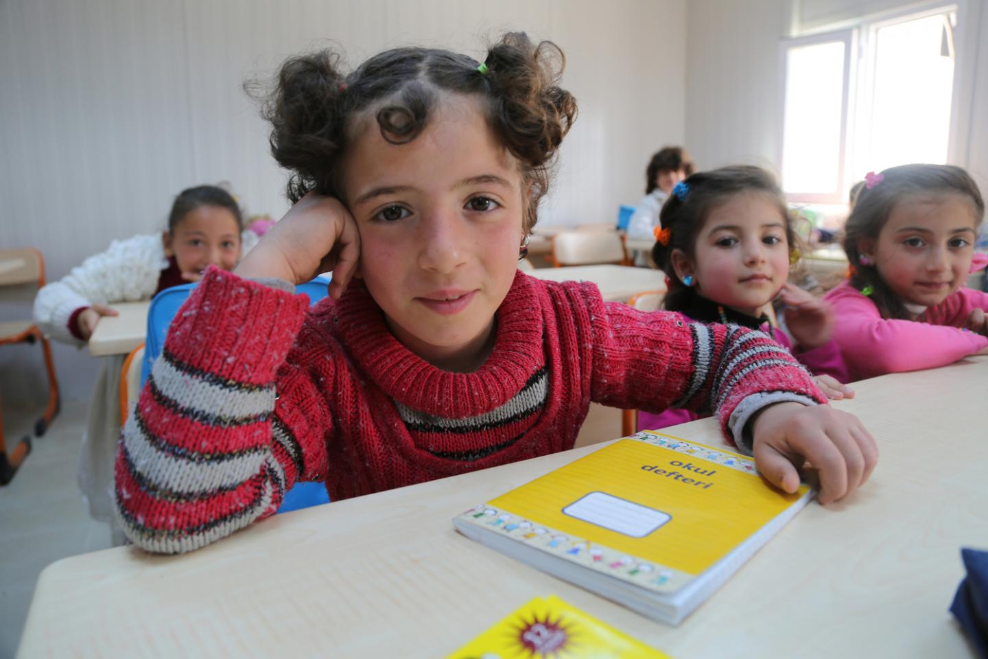 A refugee girl attends a UNICEF-support temporary education centre at a camp in Turkey