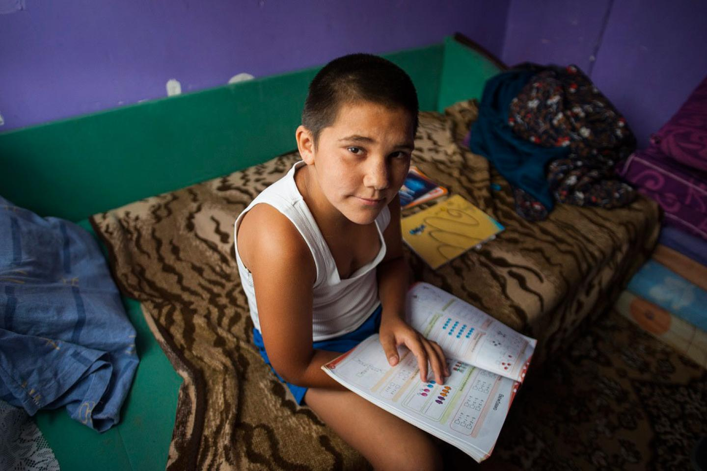 A boy sits on a bed, a school book on his lap