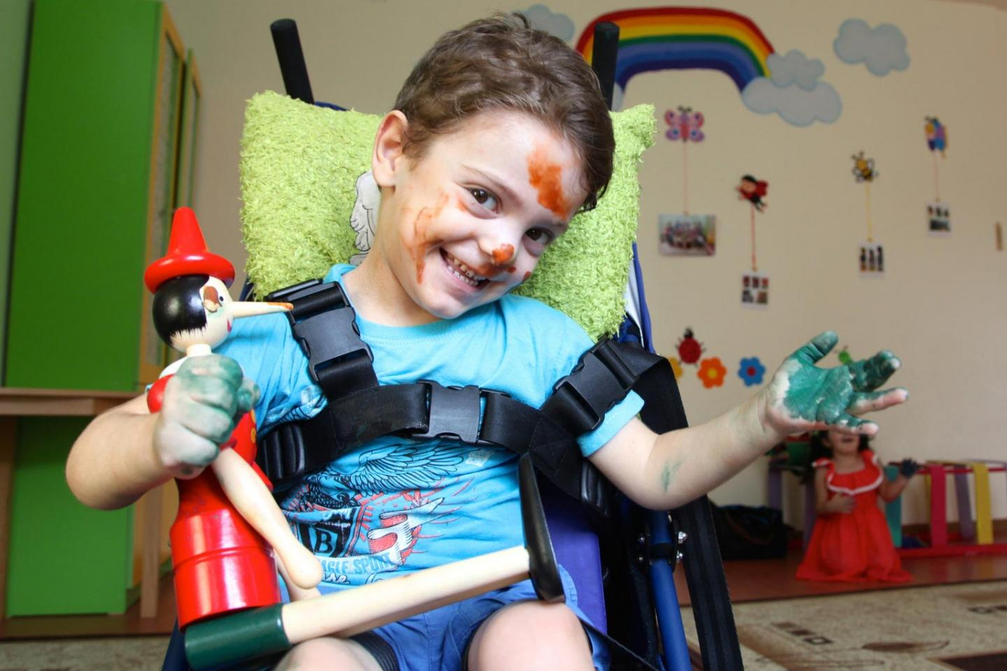 A young boy sitting in a wheelchair with paint on his hands and face, smiles at the camera.