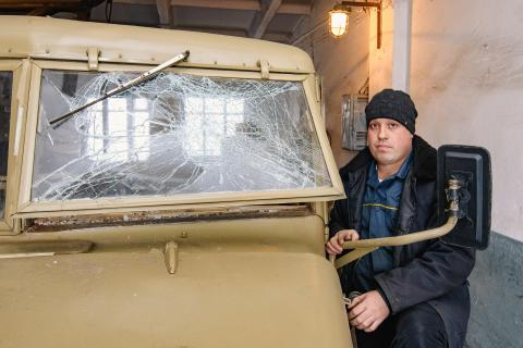 Oleksiy Dukhovy, a water worker, stands next to his truck that hit an anti-tank mine in a conflict-affected eastern Ukraine, February 2019.