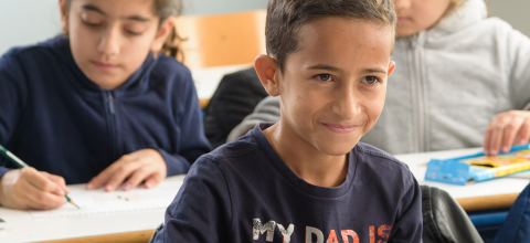 Aziz, 12 years old, smiles in a classroom.