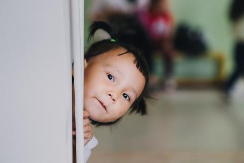 A little girl plays peek-a-boo in Kazakhstan