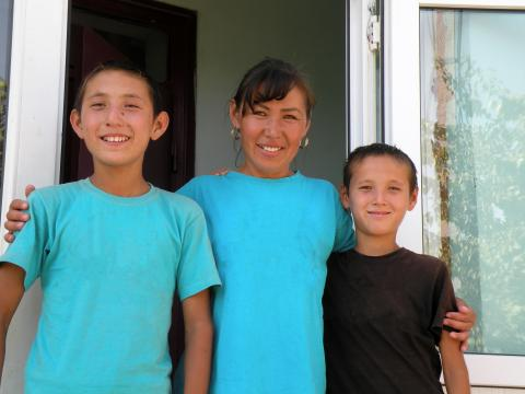 Yerbol, 10 years old, outside of his house in Shymkent, South Kazakhstan with his brother and mother.