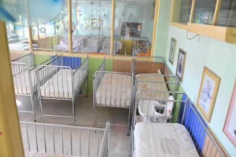 A row of empty cots where infants and toddlers deprived of parental care once slept.