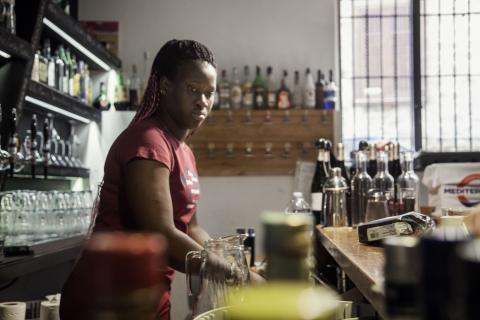 Fatou Sanneh (17) behind the coffee bar at the café where she works in Palermo, Italy.