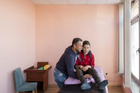 Hazir Mehmeti, helps his son Riad get back to his electric wheelchair after a physical therapy session in Handikos, a local rehabilitation center and UNICEF implementing partner.