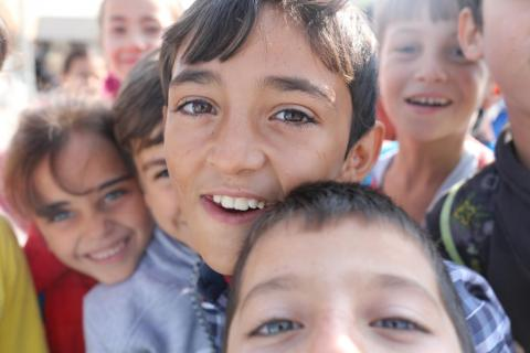 Children smile for the camera outside their school in Kilis, Turkey.