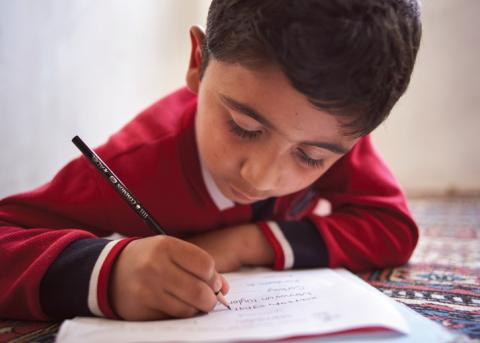 Boy at writing at a UNICEF-supported learning center in Turkey.