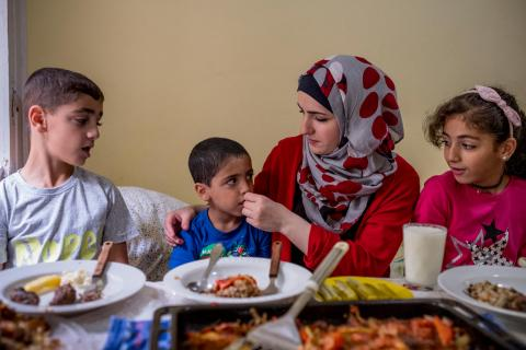 A Syrian refugee family sit down for their home made dinner at their home inside the Marienfelde emergency reception centre, Berlin, Germany.