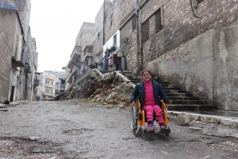 Hanaa, 8, who was paralysed by an exploding bomb and lost the use of her legs, sits in her wheelchair near her home in Sakhoor neighbourhood, east Aleppo city, Syrian Arab Republic.