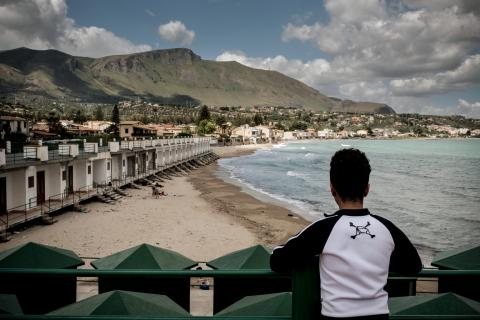 A boy who is an unaccompanied minor looks across the beach in Trabia, Italy, on May 14, 2016.