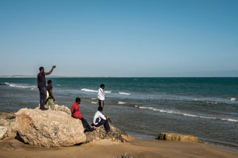 A group of Gambian boys survey the ocean from the beach in Pozzallo, Sicily