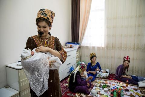 A mother in Turkmenistan holds her new baby at home during a celebration to welcome the child into the world.