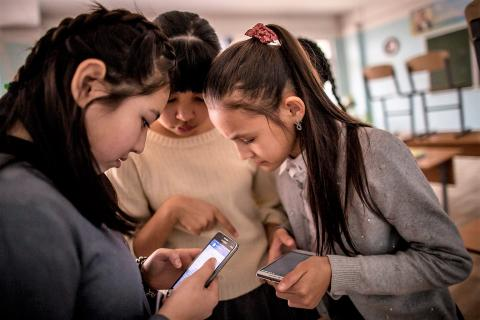 Aliya, age 13, (left) spends time with her classmates before classes begin in her school in Aktau, Kazakhstan, on 16 March 2018.