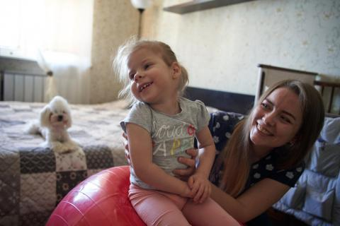 Three-year-old Agatha gets physical therapy from her mother, Ekaterina, at home in Minsk, Belarus.