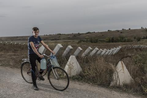 On 22 September 2018 in Ukraine, Dima Mikhalyov, 15, on his bicycle carrying water in bottles on his handlebars next to a field of antitank barriers on the outskirts of in Bakhmutka in the Donetsk region.
