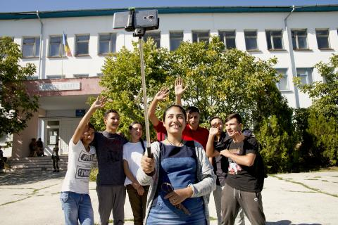 Renata, 14, takes a group selfie with her friends in front of Vulcănești school.