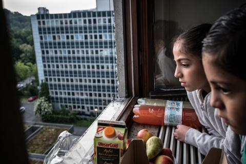 Jannat, 7 looks out of a window in their apartment in Germany.