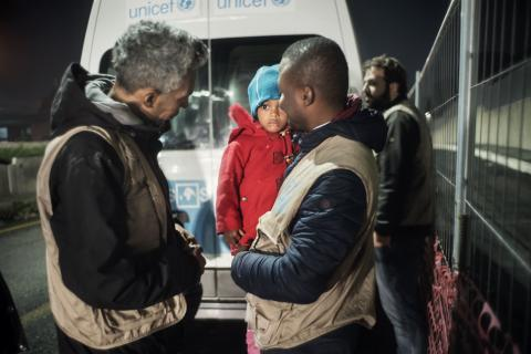 INTERSOS staffers, part of a UNICEF-supported mobile team, pick up a young girl (2) outside a building where migrants are taking shelter in Rome, Italy.