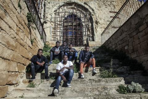 Migrant boys, who arrived in Sicily unaccompanied, pose at the remains of a church in the old town of Naro, Sicily.