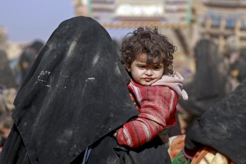 On 26 January 2019 in the Syrian Arab Republic, children and families are huddled together after being forced to flee their homes in nearby towns and villages, with their few belongings in Baghoz village in Hajin district in eastern rural Deir-ez-Zor before they embark on a long and ardous journey to safety at Al-Hol camp, almost 300km to the north.