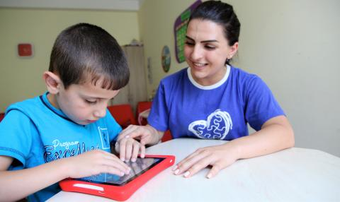 "A child using interactive learning games designed for children on the autism spectrum at the ""My Way"" Autism National Fund, Yerevan, Armenia."