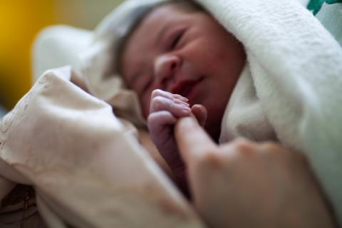 A new-born baby clutching mother's finger