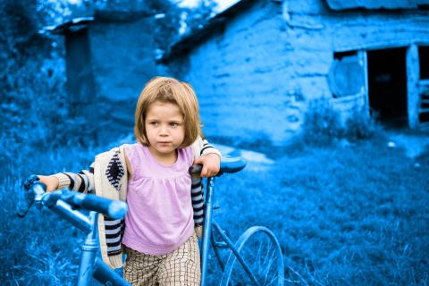 Four-year-old Flori Maria plays on a broken bike outside her family home in Romania.
