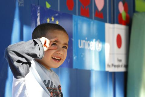 Four-year-old Mahmud from Syria sits enjoying a lovely sunny day in front of a UNICEF child-friendly space in Serbia