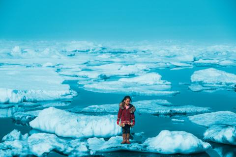 An Iñupiat girl Amaia, 11, stands on a ice floe on a shore of the Arctic.