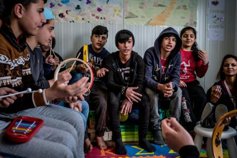 Syrian Kurdish children play musical instruments at a centre for refugees in Greece
