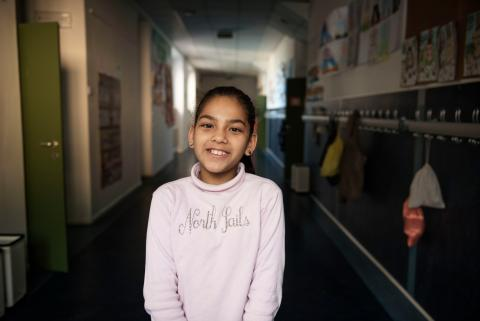 Nine-year-old Syrian refugee Badiaa stands in a corridor at the public elementary school she attends in Trento, Italy.