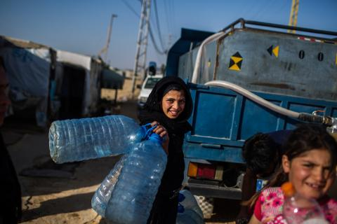 Syrian refugee girls collect water provided by UNICEF at a camp in Lebanon
