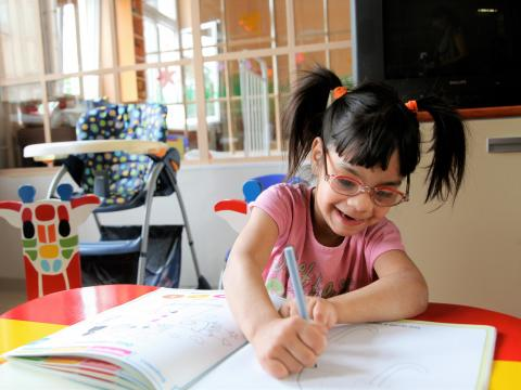 In Serbia, a girl, who has a disability, completes a learning exercise at the Zvecanksa Street centre, in Belgrade, the capital.